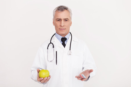 Senior grey hair doctor in uniform holding an apple in one hand and pills in another one while standing isolated on white photo