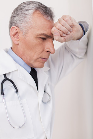 expressing negativity: Senior grey hair doctor in uniform leaning at the wall and expressing negativity