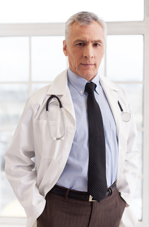 Senior grey hair doctor in uniform looking at camera and holding hands in pockets while standing isolated on white