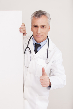 Senior grey hair doctor in uniform looking out of copy space and gesturing while isolated on white photo