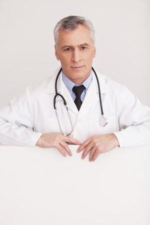 grey hair: Senior grey hair doctor in uniform looking out of copy space and smiling while isolated on white