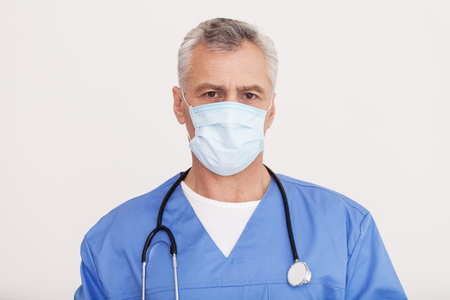 grey hair: Confident surgeon. Portrait of senior grey hair doctor in surgical mask looking at camera while standing isolated on white