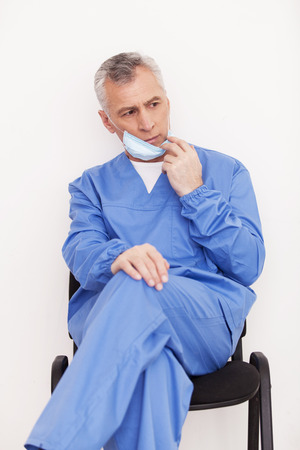 grey hair: Depressed senior grey hair doctor taking off his surgical mask while sitting at the chair 스톡 사진
