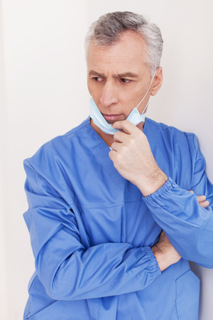 grey hair: Depressed senior grey hair doctor taking off his surgical mask while leaning at the wall