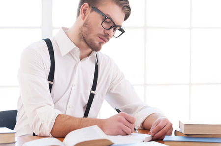 one young man: Author at work. Confident young man in shirt and suspenders writing something in note pad while sitting at his working place