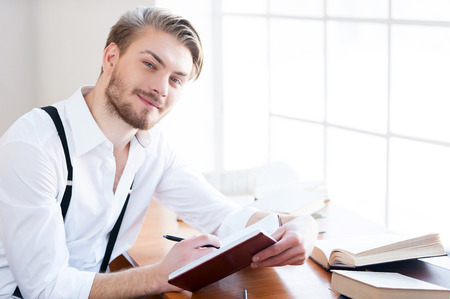 creative writer: Inspired author. Handsome young man in shirt and suspenders writing something in note pad and smiling at camera while sitting at his working place Stock Photo