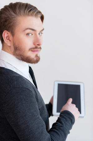 over the shoulder view: Man with digital tablet. Rear view of handsome young man holding a digital tablet and looking over shoulder while standing against grey background