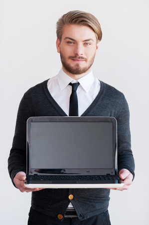 Copy space on monitor. Handsome young man holding a laptop and smiling while standing against grey background photo