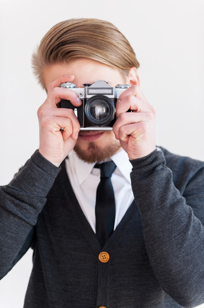 Focusing at you. Young beard man focusing at you with his retro camera while standing against grey background photo