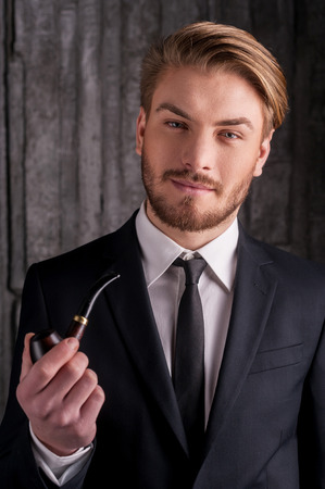 Man with a smoking pipe. Portrait of handsome young man in formalwear holding a smoking pipe and smiling at camera  photo