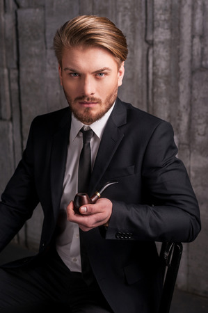 Man with a smoking pipe. Handsome young man in formalwear holding a smoking pipe and looking at camera while sitting on the chair Stock Photo
