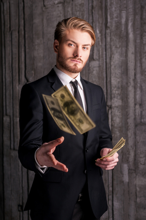 Rich and successful. Handsome young man in formalwear throwing money and looking at camera  photo