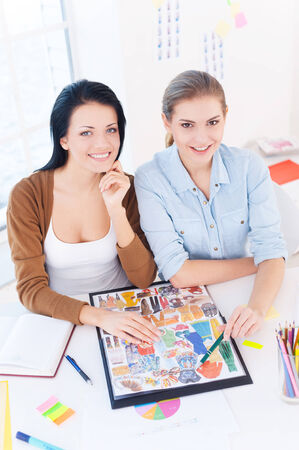 two on top: Creative executive. Top view of two young beautiful women smiling at camera while sitting at their working place