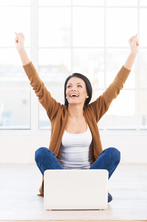 winning woman: Successful young woman. Female student with a laptop cheering in success Stock Photo