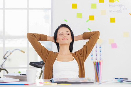 woman relaxing: Business woman relaxing. Business woman relaxing with hands behind head and smiling Stock Photo