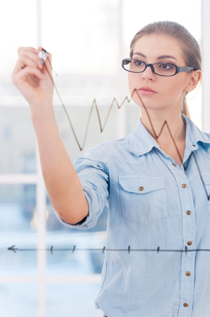 Attractive businesswoman drawing a graph  An attractive businesswoman analyst drawing a graph on a clear class wall
