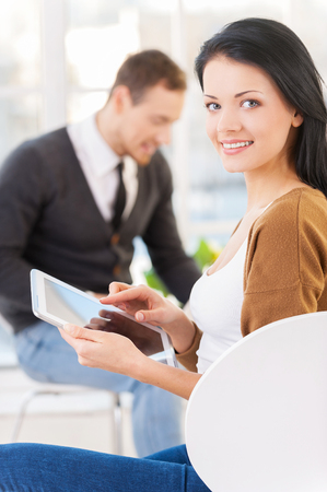 My digital assistant  Confident young businesswoman in casual wear using digital tablet and smiling while his colleagues working on the background photo