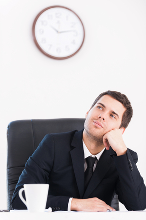 Break time. Thoughtful young man in formalwear looking away and holding head in hand while sitting at his working place with wall clock on background photo