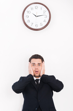 I have no time! Shocked young man in formalwear looking at camera and holding head in hands while standing under the wall clock photo
