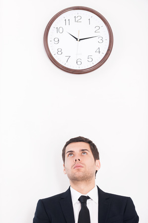 Time is money. Thoughtful young man in formalwear looking at the wall clock photo