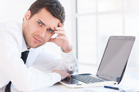 Depressed businessman. Side view of depressed young man in shirt and tie looking at camera and holding head in hand while sitting at his working place photo