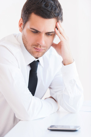 important phone call: Waiting for important call. Depressed young man in shirt and tie holding head in hand and looking at the mobile phone laying on the table Stock Photo