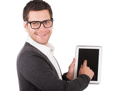Let me show you all features of this gadget! Cheerful young man holding a digital tablet and pointing it while standing isolated on white photo