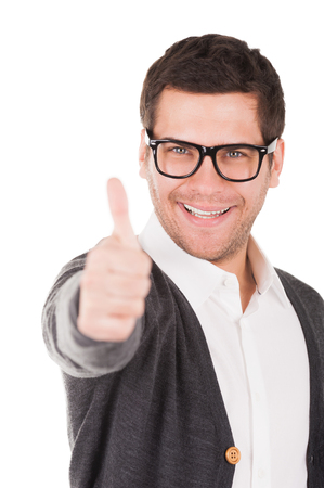 Everything is good! Handsome young man holding showing his thumb up and smiling while standing isolated on white photo