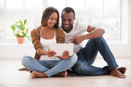 position d amour: Travailler � leur nouvelle tablette. Belle jeune couple africain en utilisant tablette num�rique tout en restant assis ensemble sur le sol � leurs appartements