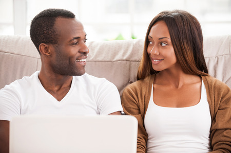 Spending their free time in the net. Beautiful young African couple sitting on the couch and looking at each other while using laptop together Stok Fotoğraf