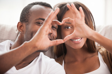 We love each other! Beautiful young African couple sitting close to each other and looking through a heart shape made with their fingers photo
