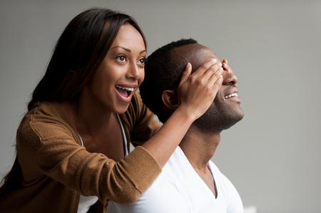 あなたの驚きを持って!美しい若いアフリカ女性の手で彼女のボーイ フレンドの目を覆っていると笑みを浮かべながら、灰色の背景上に分離されて