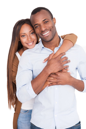 We love each other! Beautiful young African woman hugging her boyfriend and looking at camera while standing isolated on white
