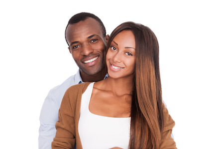 Happy to be together. Beautiful young African couple standing close to each other and smiling at camera while isolated on white  photo