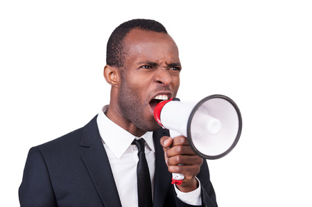 Furious boss. Angry young African man in formalwear shouting at megaphone while standing isolated on white background  photo
