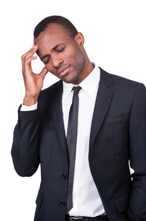 Tired businessman. Young African man in formalwear touching his head with hand and keeping eyes closed while standing isolated on white background  photo