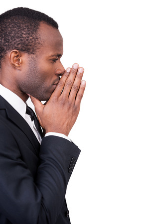 chin on hands: Thinking about new solutions. Side view of thoughtful young African man in formalwear touching his chin with clasped hands while standing isolated on white background