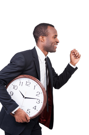Confidence and punctuality. Side view of cheerful young African man in formalwear running with clock in his hand and isolated on white background  photo