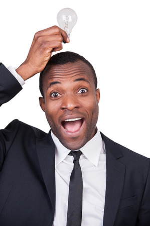 I have an idea! Cheerful young African man in formalwear holding a light bulb upon his head and smiling while standing isolated on white background  photo