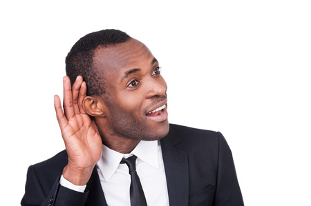 What did you say? Cheerful young African man in formalwear holding hand near ear and smiling while standing isolated on white background  photo
