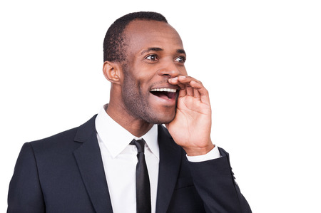 Announcing the good news. Cheerful young African man in formalwear holding hand near mouth and shouting while standing isolated on white background  photo