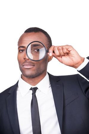 Businessman examining you. Serious young African man in formalwear looking through a magnifying glass while standing isolated on white background  photo