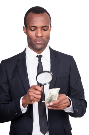 Real or fake? Serious young African man in formalwear looking through a magnifying glass at the paper currency while standing isolated on white background  photo