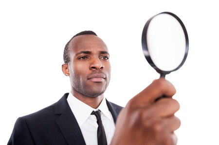 Examining something. Low angle view of serious young African man in formalwear looking through a magnifying glass while standing isolated on white background  photo