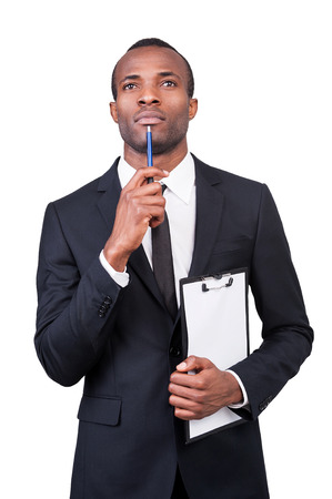 Thoughtful businessman. Thoughtful young African man in formalwear holding a clipboard and pen while standing isolated on white background