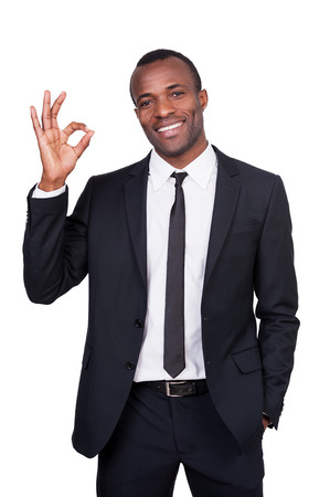 ok sign: Gesturing OK sign. Handsome young African man in full suit showing OK sign and smiling while standing isolated on white background