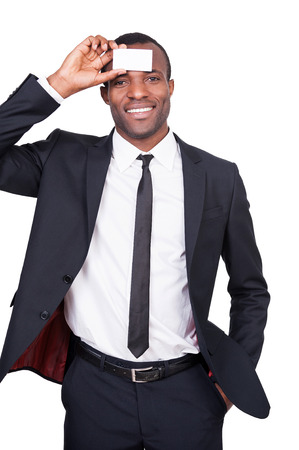 Copy space on my forehead. Handsome young African man in formalwear holding his business card at forehead and smiling while standing isolated on white background  photo