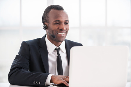 of african descent: Customer service representative at work. Cheerful young African man in formalwear and headset working on laptop and smiling Stock Photo