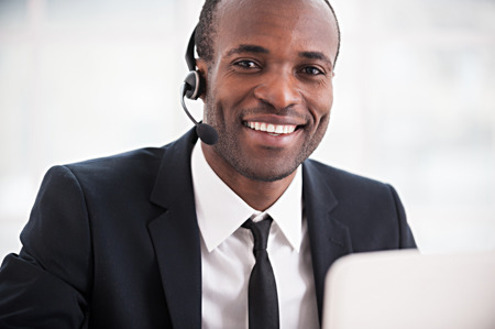 Customer service representative. Cheerful young African man in formalwear and headset working on laptop and smiling at camera photo