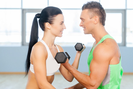 couple exercising: Fitness couple in the gym exercising in gym and looking at each other